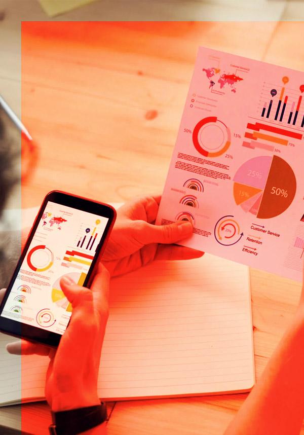 Personne lisant des statistiques de son site web sur son smartphone et une feuille pour optimiser sa visibilité